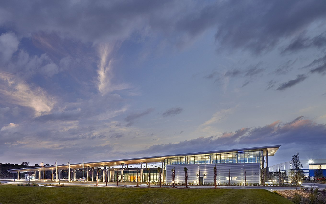 Boeing Welcome Center Sheltering Roof Resembling an Airplane Wing over Walkway and Building at Dusk